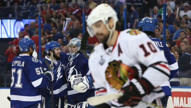 Tampa Bay Lightning goalie Andrei Vasilevskiy (88) celebrates with teammates as Chicago Blackhawks left wing Patrick Sharp (10) skates off the ice after game two of the 2015 Stanley Cup Final at Amalie Arena.
