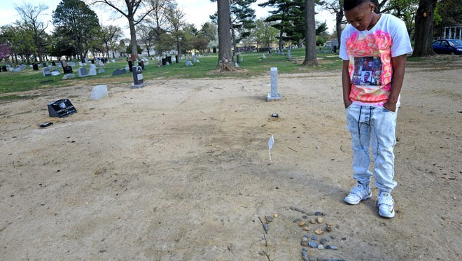 On the one-year anniversary of Troy Anderson's murder, his cousin Mumchie Anderson, 17, spelled out his name in stones at Harleigh Cemetery in Camden.