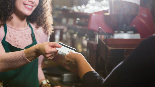 Cropped view of a cashier, a young woman, working in a coffee shop, taking a credit card or gift card from a customer. The main focus is on the hands and the card.