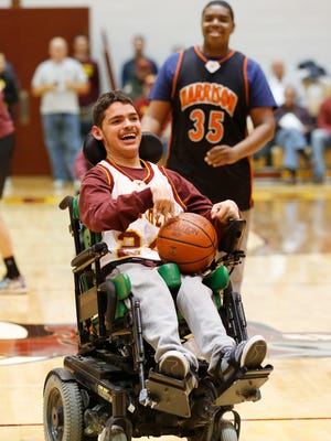 "Javier Casas of the McCutcheon Unified team smiles as he brings the ball up court during the Champions Together Unified basketball game Friday, December 18, 2015, at McCutcheon High School. Special needs students from Harrison and McCutcheon took part in the game. The slogan for the game was ""Spread the word to end the word."" Students are asked to stop using the word ""retarded,"" which has been found to be hurtful to special needs students."