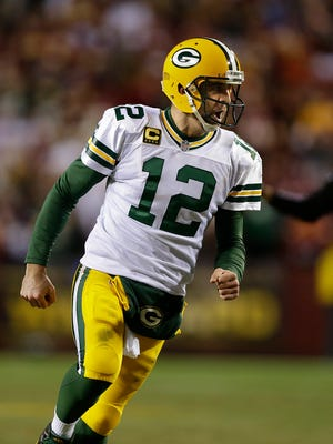Green Bay Packers quarterback Aaron Rodgers (12) celebrates after throwing a touchdown pass against Washington Redskins during the NFC wild-card round playoff game.