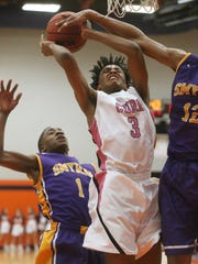 Blackman's James Polite (3) goes up for a shot as Smyrna's Tae Brady (1) and Myles Kumrow (12) defend against him on Tuesday, Feb. 7 2017, at Blackman.
