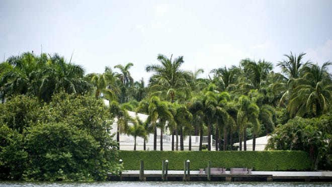 Viewed from the Intracoastal Waterway, a high hedge shields the former home of the late convicted sex offender Jeffrey Epstein at 358 El Brillo Way.