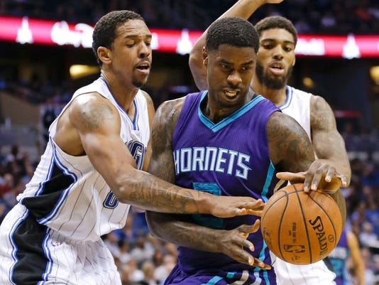 Orlando Magic forward Channing Frye, left, fouls Charlotte Hornets' Marvin Williams, center, as they battle for a loose ball during the first half of an NBA basketball game, Saturday, Jan. 3, 2015, in Orlando, Fla. (AP Photo/John Raoux)