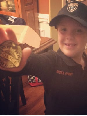 Ayden Perry, 5, holds a police badge, while wearing his Medina Police Department shirt and hat Friday night.