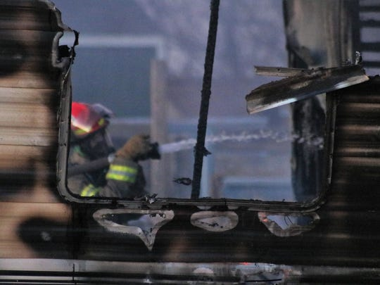 A Tularosa Volunteer Fire Department firefighter conducts mop up operations of a trailer fire in the 1500 block of Sixth Street Thursday.