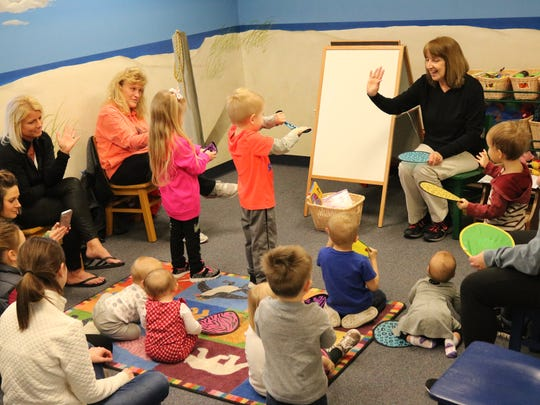 "Terri Winke, preschool coordinator for the Ida Rupp Public Library, sings along with local children at the weekly ""Babies and Books"" program on Wednesday."