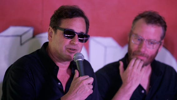 Bob Saget speaks during a press conference at the Bonnaroo Music & Arts Festival  on  Sunday, June 16,  2013 in Manchester, Tenn. Matt Berninger from the Nationals sits next to Saget.