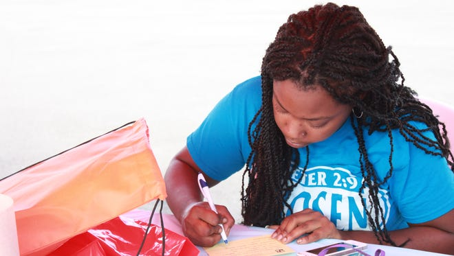 Ashley Croom fills out information requests Friday at the 'Back to School Bash' held by the University of Tennessee at Martin Jackson Center at Walgreens.