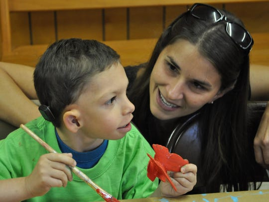 Rebecca Ebert talks to her son, Hendrix, while he paints a butterfly during VBS at Elwood Baptist Church.