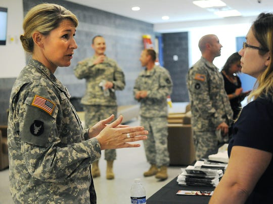 Maj. Kristen Auge talks to a representative of the Minnesota National Guard's 347th Regional Support Group on Wednesday for Women's Equality Day at Camp Ripley.