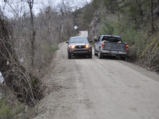Two pickups, one in the ditch, pass each other Thursday on the narrow stretch of Baxter County Road 63 where Brandon Wolf was killed Sunday when his truck rolled down the embankment into the North Fork River.
