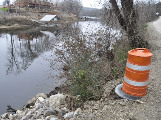 Rocks and boulders stabilizing Baxter County Road 63, which allowed for the roadway to be widened, stop just 20 feet from where Brandon Wolf's truck went off the road into the North Fork River on Sunday.