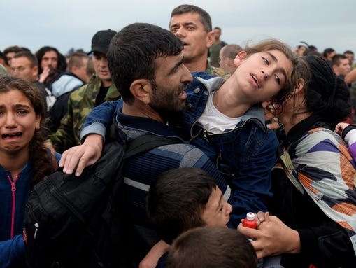 Migrants and refugees break through a cordon of Macedonian