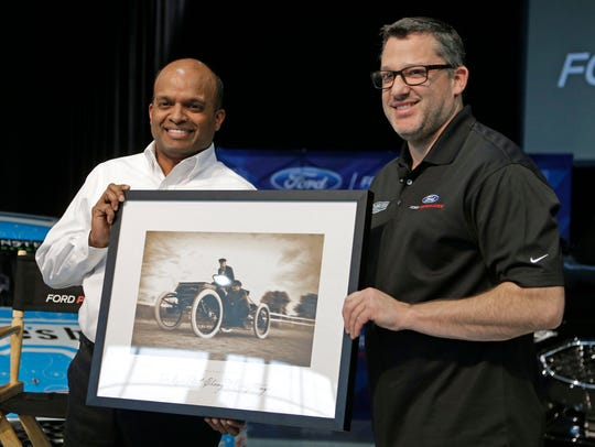 Team owner Tony Stewart, right, poses with Raj Nair,