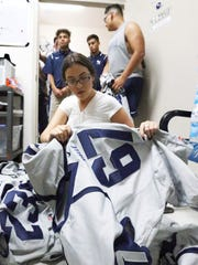 Hannah Dominguez, Del Valle football team manager, helps distribute newly arrived Nike jerseys to the team Wednesday. The players also received a Nike brand wind suit, compression shirt and polo shirt, said head coach Jessie Perales.