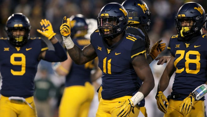 FILE - In this Oct. 25, 2018, file photo, West Virginia linebacker David Long Jr. (11) celebrates with his teammates after sacking Baylor's quarterback during the first half of an NCAA college football game, in Morgantown, W. Va. The Mountaineers' leading tackler is coming off his best game of the season. He had four tackles for loss and three sacks in a rout of TCU last week. (AP Photo/Raymond Thompson, File)