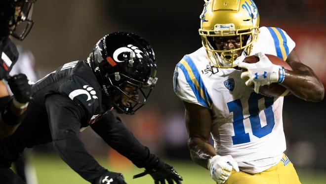 Cincinnati safety Darrick Forrest forces UCLA wide receiver Demetric Felton (10) out of bounds during the second half of an NCAA college football game Thursday, Aug. 29, 2019, in Cincinnati. (Albert Cesare/The Cincinnati Enquirer via AP)