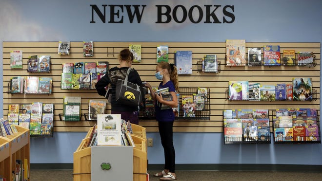 Kaylee Webb, 9, and her mother, Kindsey Logan, look over the selection of new books Wednesday in the children's section of the Burlington Public Library.