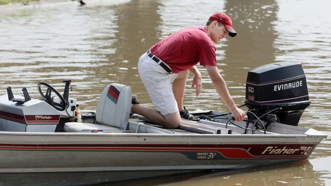Jacob Yochum test the outboard motor on a boat that his father, Tim, is passing on to him Thursday in Burlington. Jacob will the third generation family member to own the boat which was bought by his grandfather new in 1988.