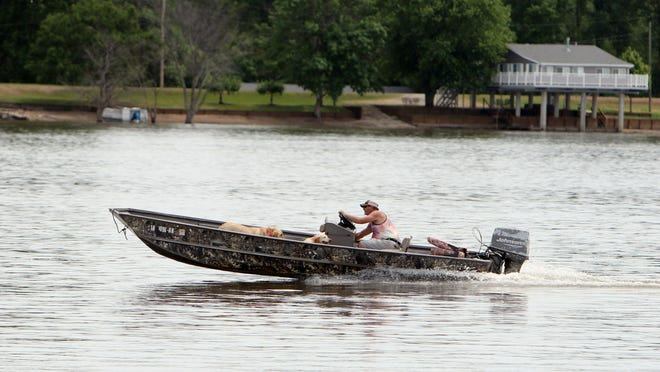 A boater travels along the Mississippi River Friday in Burlington. A flood warning is now in effect until Wednesday. By Friday morning, the river stage in Burlington was 15.5 feet and steady, with minor flooding occurring.