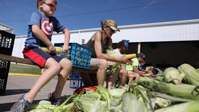 Wyatt Workman, 6, of Donnellson, and his grandmother, Earny Hotop of West Point shuck ears of corn while taking part in Shuck Fest 2018 at the Merschman Seeds facility ahead of the West Point Sweet Corn Festival. This year's Sweet Corn Festival has been canceled due to COVID-19.
