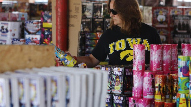 Sandi Smith, picks up a section of fireworks for sale at the Castle Fireworks tent Wednesday in the parking lot near City Center shopping area on Mont Pleasant Street. Fireworks will be sold at the tent through July 8th. Firework sales have increased throughout the United State this season. Tent managers Misti Kelley and McKenzie Shrum remind customers that it is illegal to use or explode fireworks in the city limits of Burlington.