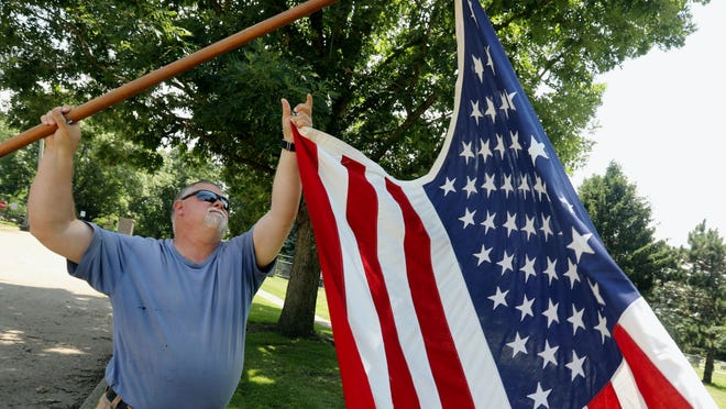Mike Bloomer, administrator at Aspen Grove Cemetery, takes down one of two American Flags that he put up outside the Sunnyside Avenue entrance Thursday in Burlington. Bloomer recently began a new tradition of flying the American flags at the entrance of the cemetery, to honor veteran when they are buried.