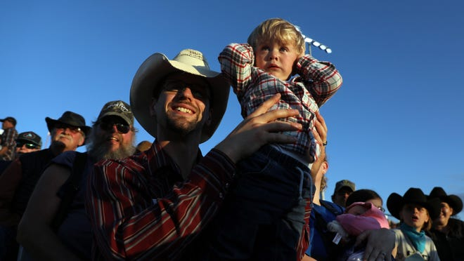 In this photo from last year's Tri-State Rodeo, D.J. Meyer of Palo holds his son, Joshua Meyer, 2, as fireworks go off at the start of the Tri-State Rodeo CINCH Chute-Out Sept. 4, 2019, at the C.E. Richards Arena in Fort Madison. The Lee County Board of Health is urging for the cancellation of large-scale events, including the Tri-State Rodeo, due to COVID-19 concerns.