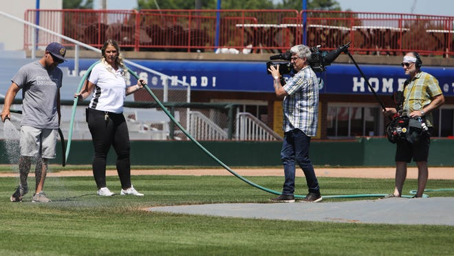 """Jordan Barr, the head groundskeeper for the Burlington Bees Minor League Baseball team, is assisted by Burlington Bees general manager Kim Parker Monday as the two are filmed by a crew from the NBC News Chicago bureau made up of Steve Azzato, director of photography and Adam Zletz, audio technician, at Community Field. The two men were filming and collecting audio for an upcoming segment that will air on the Sunday edition the """"Today Show."""""""