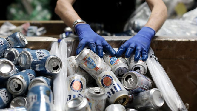 Russell Elliott sorts cans at the Hope Haven Redemption Center after the facility reopenied on a limited basis with policy changes June 4 in Burlington.