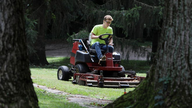 Daniel Crooks, a summer hire with the City of Burlington Parks and Recreation Department, mows the grass around the former horseshoe courts Monday in Crapo Park. It takes Crooks five days to mow the park. Parks Superintendent Ryan Gourley is currently looking to hire two people to fill positions within the department.