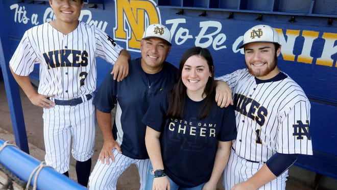 Notre Dame High School baseball coach Chris Chiprez, surrounded by his children Carson, 16, Bella, 16 and Drew, 18, in the team's dugout, Thursday July 23, 2020 at Winegard Field.
