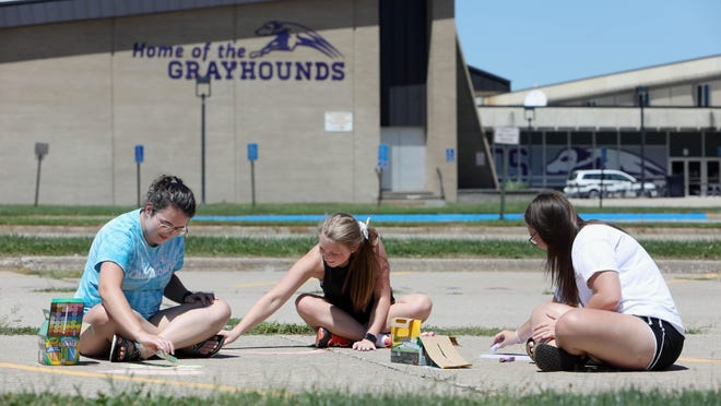 From left, recent Burlington High School graduates Elena AbouAssaly, Kaylin Moeller and Karly Cook, all former band members, make chalk drawings in the school's parking lot Tuesday in Burlington. The three were passing the time while waiting for fellow music students to show up and sign a gift to give the school's music teachers Derrick Murphy, Diana Wells and James Flaherty.