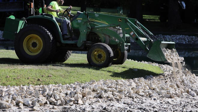 Cody Wehrle dumps erosion stones from a loader as workers with the City of Burlington Parks and Recreation department were replacing the limestone border stones with erosion stones Wednesday at Lake Starker in Crapo Park. The park was drained several feet to allow the work to take place. The limestone border stones will eventually be used within the parks system.