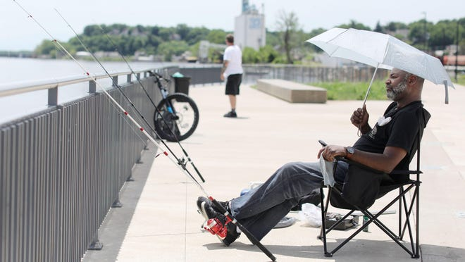 John D Taylor keeps cool under an umbrella June 5 while fishing along the Mississippi riverfront in Burlington. Temperatures soared higher than normal across much of the nation in June and through the first six months of 2020, putting the country on track for what could be another one of its warmest years on record. In Iowa, June's average temperature -- 72.9 -- was 3.8 degrees warmer than the previous century's average.