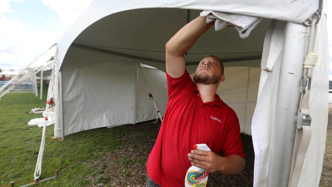 Erik Rudd, tent manager for Kempker's True Value of Fort Madison, wipes down a tent for merchandise sales Tuesday while setting up for the RiverFest 2020 music festival at Riverview Park in Fort Madison. The tent was one of 10 he set up, ranging in size from 15 feet by 15 feet to 150 feet by 60 feet.