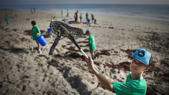 Gavin Lobrutto, 9, holds up a shoe he found while he and his third grade classmates took part in a beach cleanup with Friends of Palm Beach at the public beach near Clarke Avenue in February.