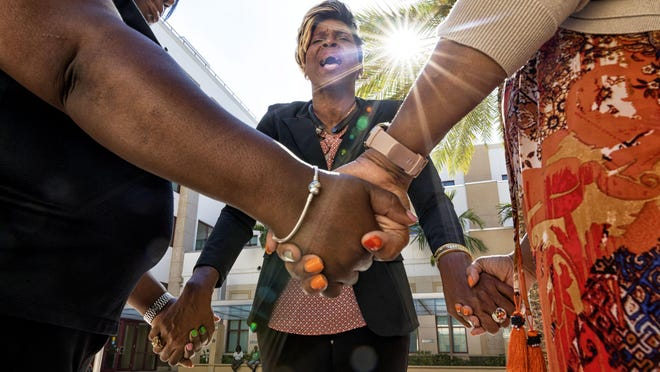 Pastor Dr. Linda Collymore, center, leads a prayer with minister Lakeshia Gilbert, left, and pastor Tanya Benjamin, right, outside city hall in West Palm Beach, Florida on August 19, 2019. The purpose is to (Sound the Alarm) that the Clergy will no longer sit on the sidelines and watch our neighborhoods deteriorate.