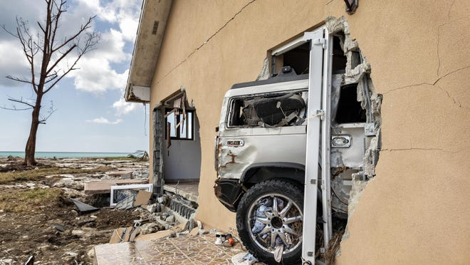 A Hummer sticks out of the garage wall at a home damaged by Hurricane Dorian in Freeport, Bahamas on September 17, 2019.