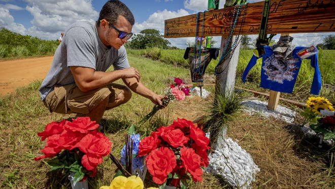 Kris Meyer lays some flowers on a roadside memorial for his friends Brandon Rollins, Damion Tillman and Keven Springfield along Lake Streety Road in Frostproof on Tuesday. The three men had gone to Lake Streety to fish Friday night where they were shot and brutally beaten in a triple homicide that's shocked the small Polk County community. Law enforcement is now offering a $30,000 reward for information that leads to an arrest.