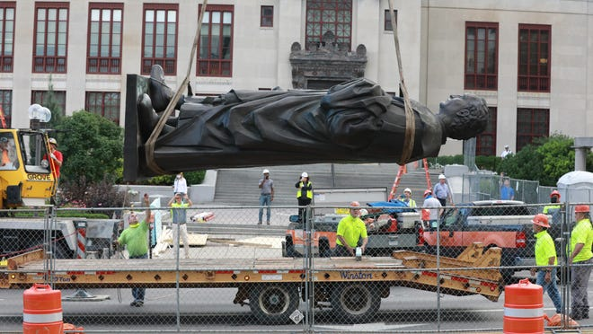 Workers place the Christopher Columbus statue onto a flatbed truck after removing it from its pedestal in front of Columbus City Hall on Wednesday morning. It will be put in a city storage facility, over objections from some Italian Americans living nearby.