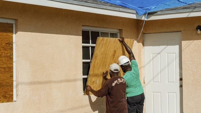 Residents cover a window with plywood in preparation for the arrival of Hurricane Isaias, in the Heritage neighborhood of Freeport, Grand Bahama, Bahamas, Friday, July 31, 2020.