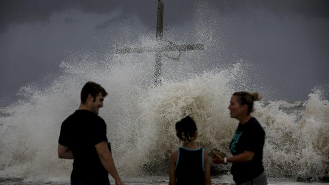 People talk as waves wash ashore and the outer bands of Hurricane Laura bring winds and rain Wednesday, Aug. 26, 2020, in High Island.