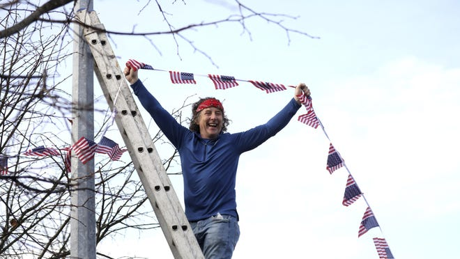 A man puts bunting up in the town of Ballina,  the ancestral home of Joe Biden, in North West of Ireland, Saturday, Nov. 7, 2020. Biden was elected Saturday as the 46th president of the United States, defeating President Donald Trump in an election that played out against the backdrop of a pandemic, its economic fallout and a national reckoning on racism.