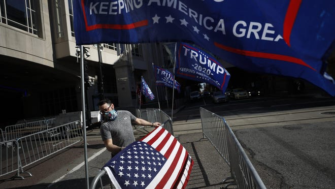 A man sets up flags Monday as supporters of President Donald Trump protest outside the Pennsylvania Convention Center, where vote counting continues.