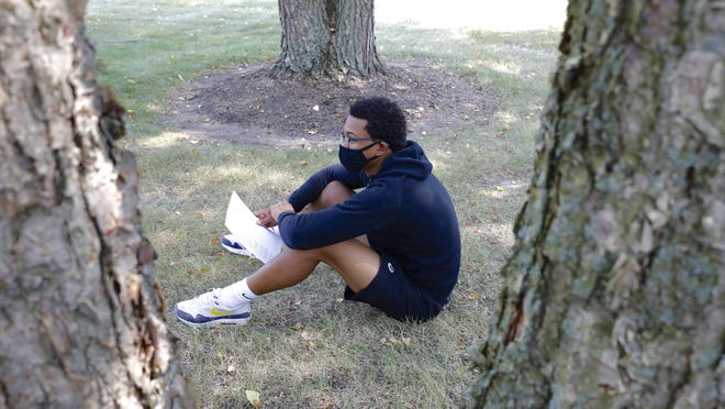Dathan Wickson Jr. attends English class on Monday in the courtyard at Boylan Catholic High School in Rockford. Students and teachers are able to take a break from face masks at school when they are outside and can maintain a social distance of six feet or more.