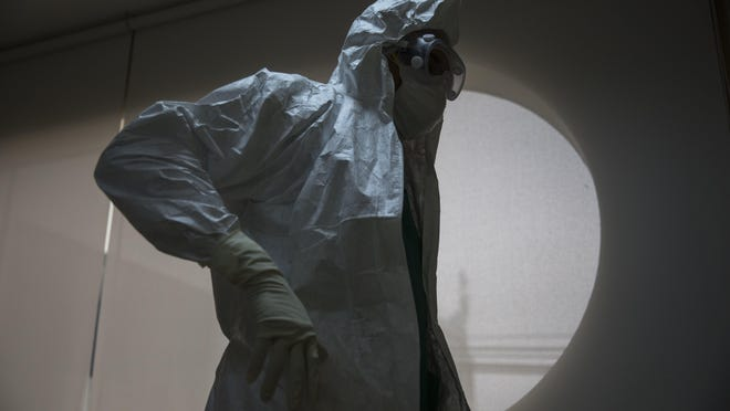 A doctor dons protective gear before entering an intensive care unit for COVID-19 cases at a hospital in Lima, Peru.