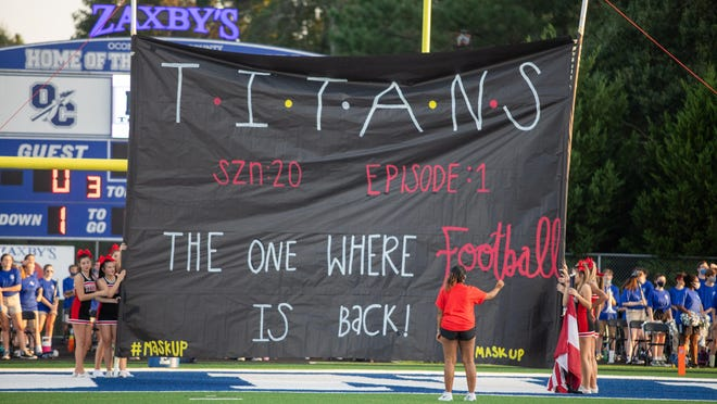 A student makes last minute adjustments to the banner during a high school football game between North Oconee High School and Oconee County High School in Watkinsville, Ga. on Friday, Sept. 4, 2020. The Oconee County Warriors won 27-7.