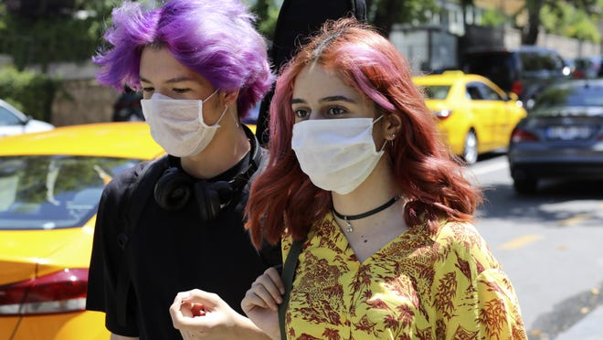 Young people wearing face masks to protect against the spread of coronavirus, walk in Ankara, Turkey, Friday, June 26, 2020. Turkish authorities have made the wearing of masks mandatory in most of the country to curb the spread of COVID-19 following an uptick in confirmed cases since the reopening of many businesses.